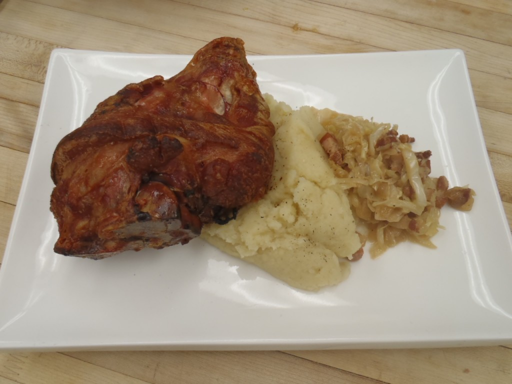A roast ham hock with mash potatoes and braised cabbage