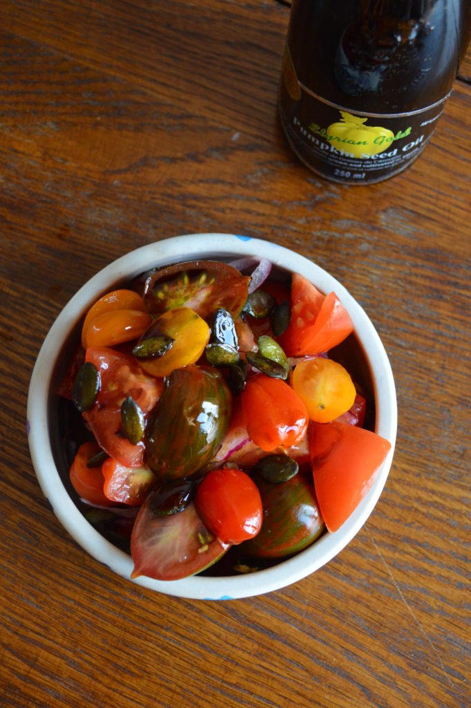 Tomato salad garnished with Styrian pumpkin seed oil.