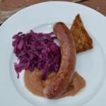 A plate of sausage, toast, apple sauce, and braised red cabbage.