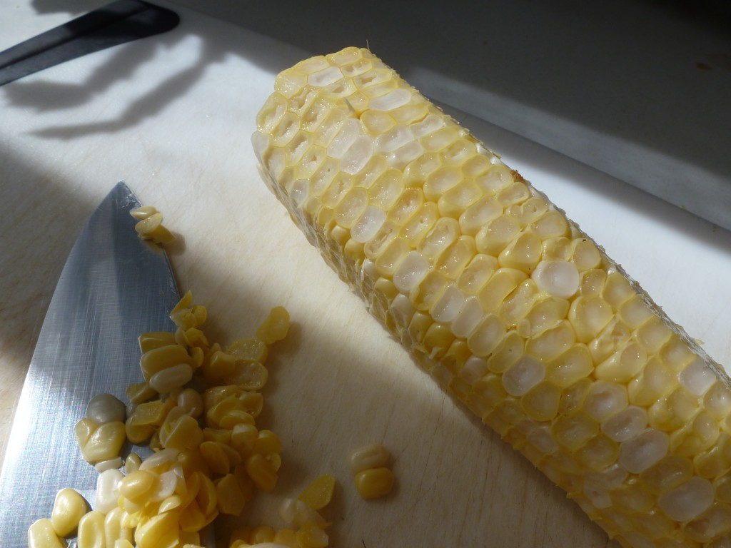 Cutting the tips of the corn kernels to expose the interior