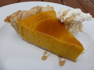 A slice of pumpkin pie with maple syrup and whipped cream