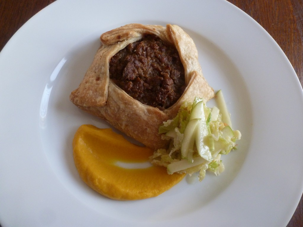 An individual tourtière, with pumpkin purée and Savoy cabbage