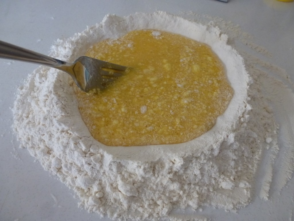 Slowly incorporating the flour into the eggs