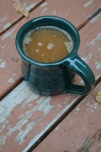 A mug of frothy, steaming mulled cider.