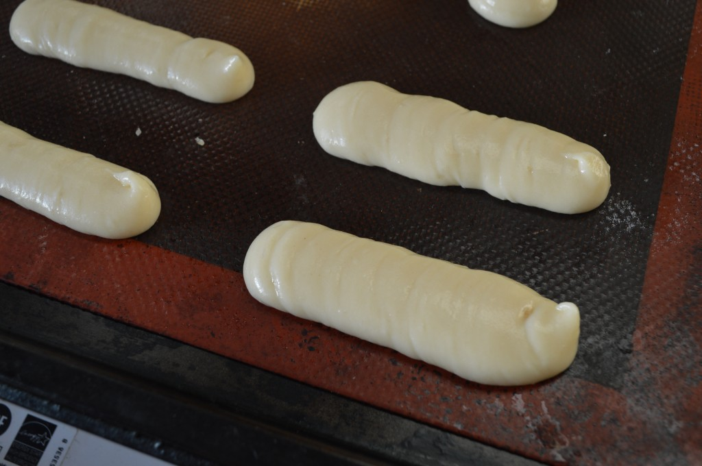 Piping choux pastry to make éclairs