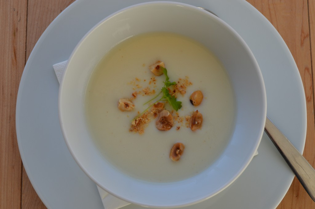 Bowl of parsnip and pear soup, garnished with toasted hazelnuts and chervil