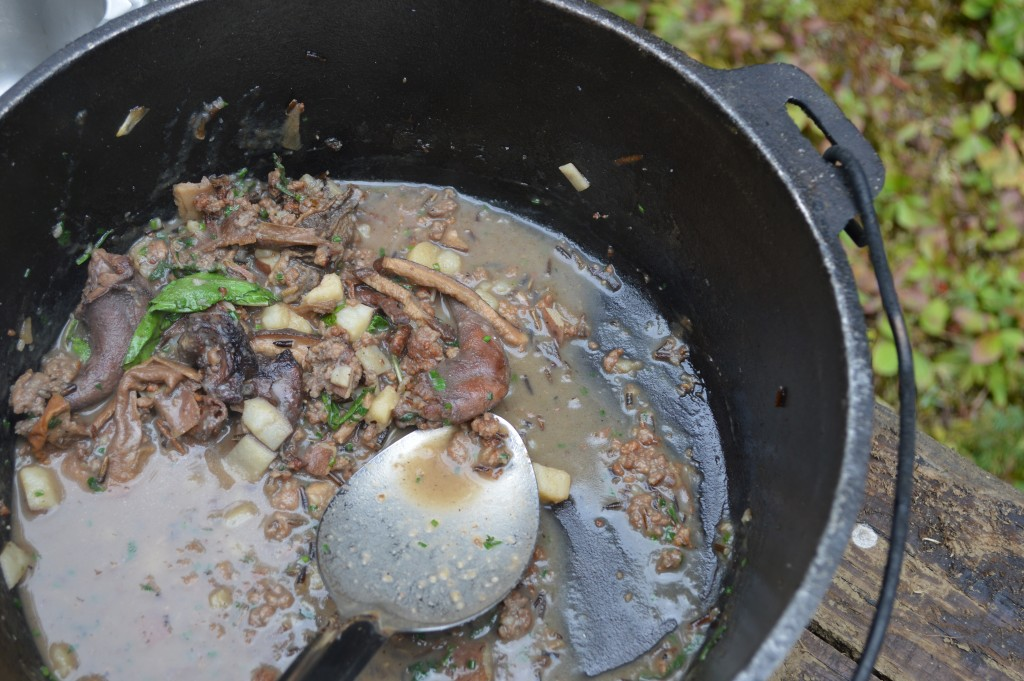Squirrel stew in a pot over the fire.