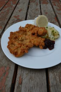 Pork schnitzel with parsley potatoes, cranberry, and lemon.