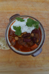 A bowl of chili with sour cream and cilantro.