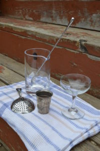 The equipment required for a stirred cocktail: mixing glass, barspoon, and julep strainer.