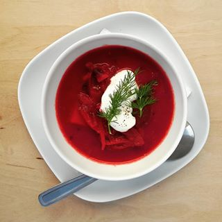 A bowl of borscht with sour cream and dill.