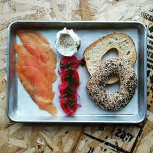 A platter of cured salmon, bagel, cream cheese, and vegetables.