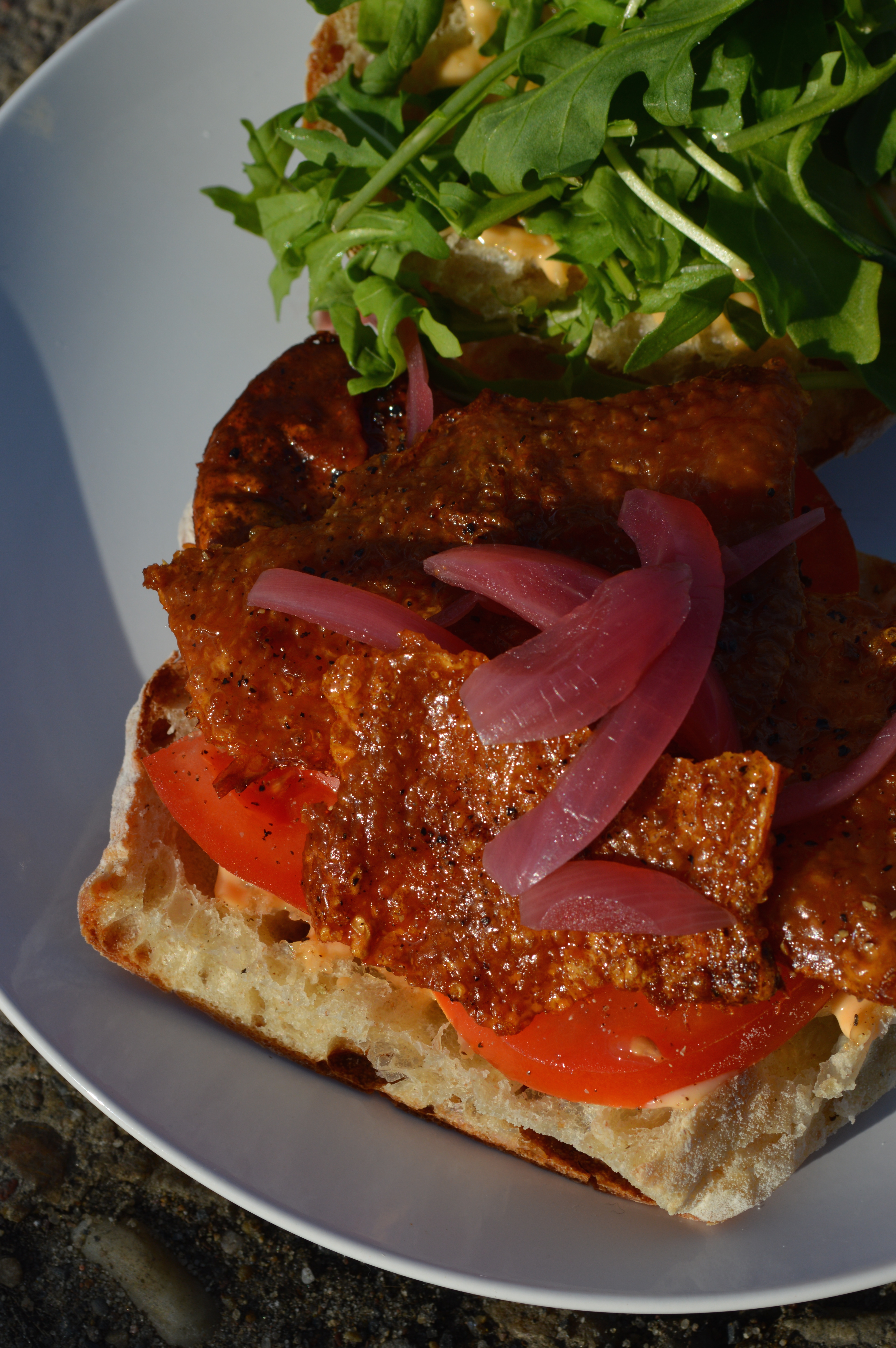 A sandwich made with tomato, chili mayo, pickled onion, and crispy chicken skin.